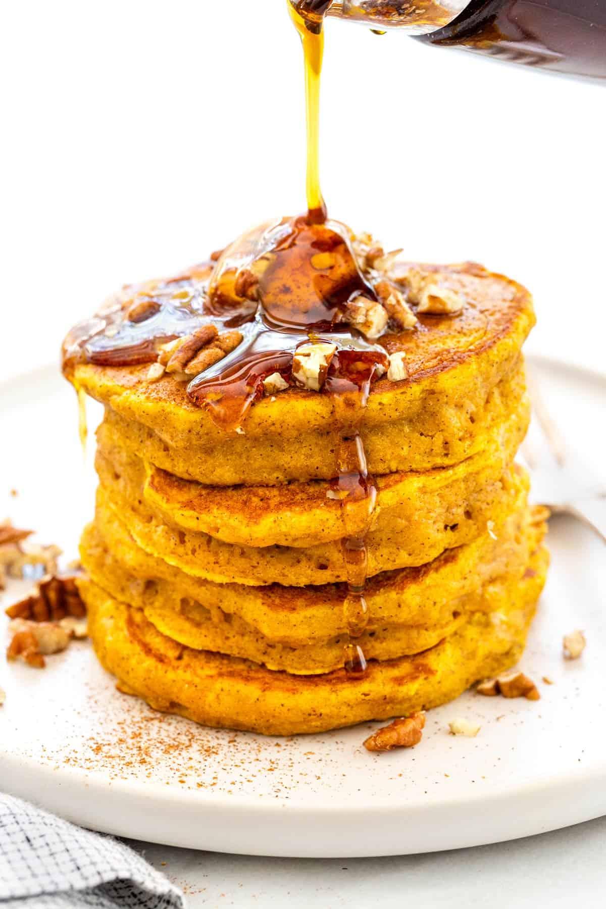 Light and fluffy pumpkin pancakes mixed with a warm blend spices. Using pumpkin puree keeps each cake tender and adds a festive orange hue. #pumpkinpancakes #pancakes #breakfast #pumpkinrecipes