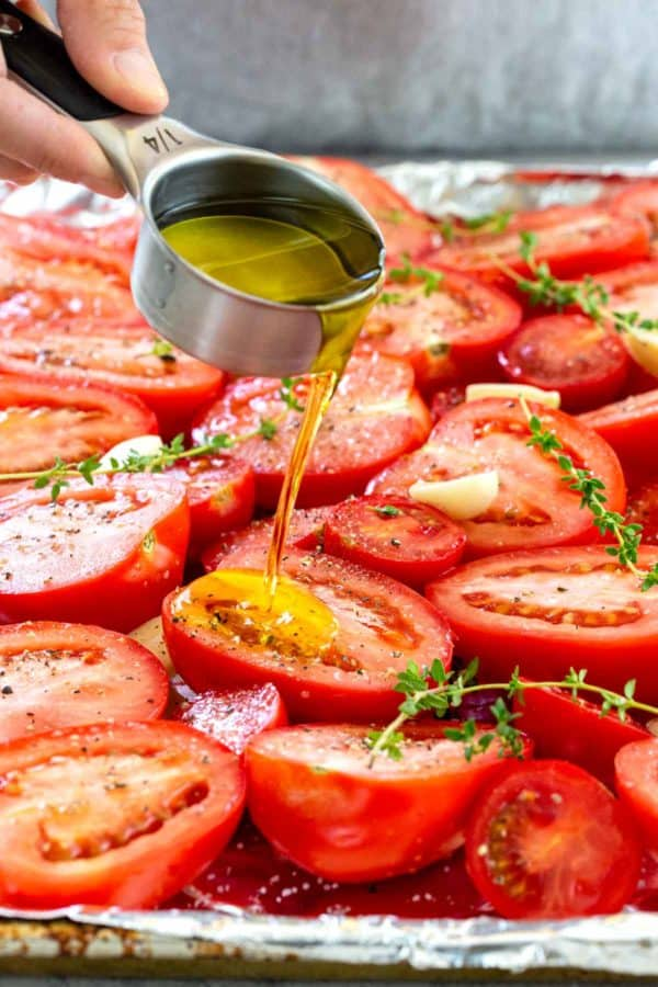 pouring olive oil over sliced tomatoes on a baking sheet