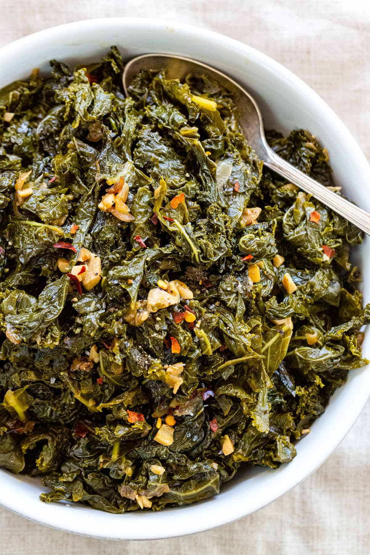 Braised kale is a simple way to tenderize and deepen the flavor. The greens first saute to maximize the aromatics in the dish then get covered and simmer. #kale #braisedkale #healthyrecipes #sidedish