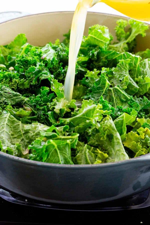 pouring braising liquid into a pot with chopped kale