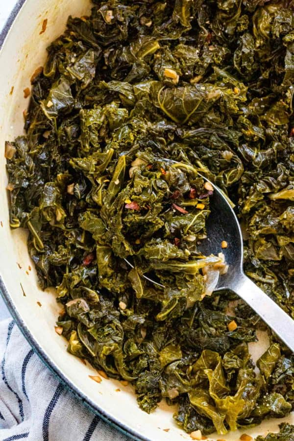 stirring braised kale with a cooking spoon