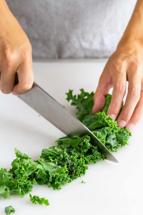 chopping kale on a butting board with a chefs knife