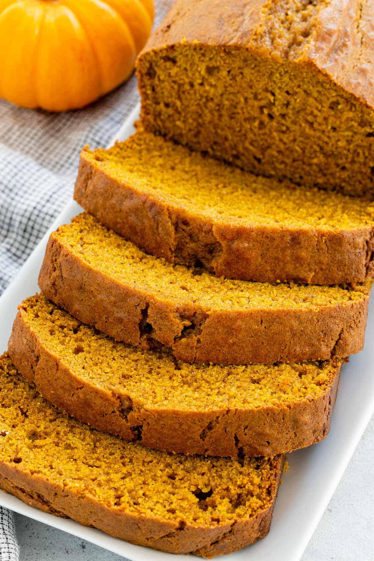 Easy pumpkin bread recipe made with pumpkin puree, dark brown sugar, sour cream, and little cornstarch. A tender quick-bread with beautiful dome top. #pumpkinbread #pumpkinrecipe #bread