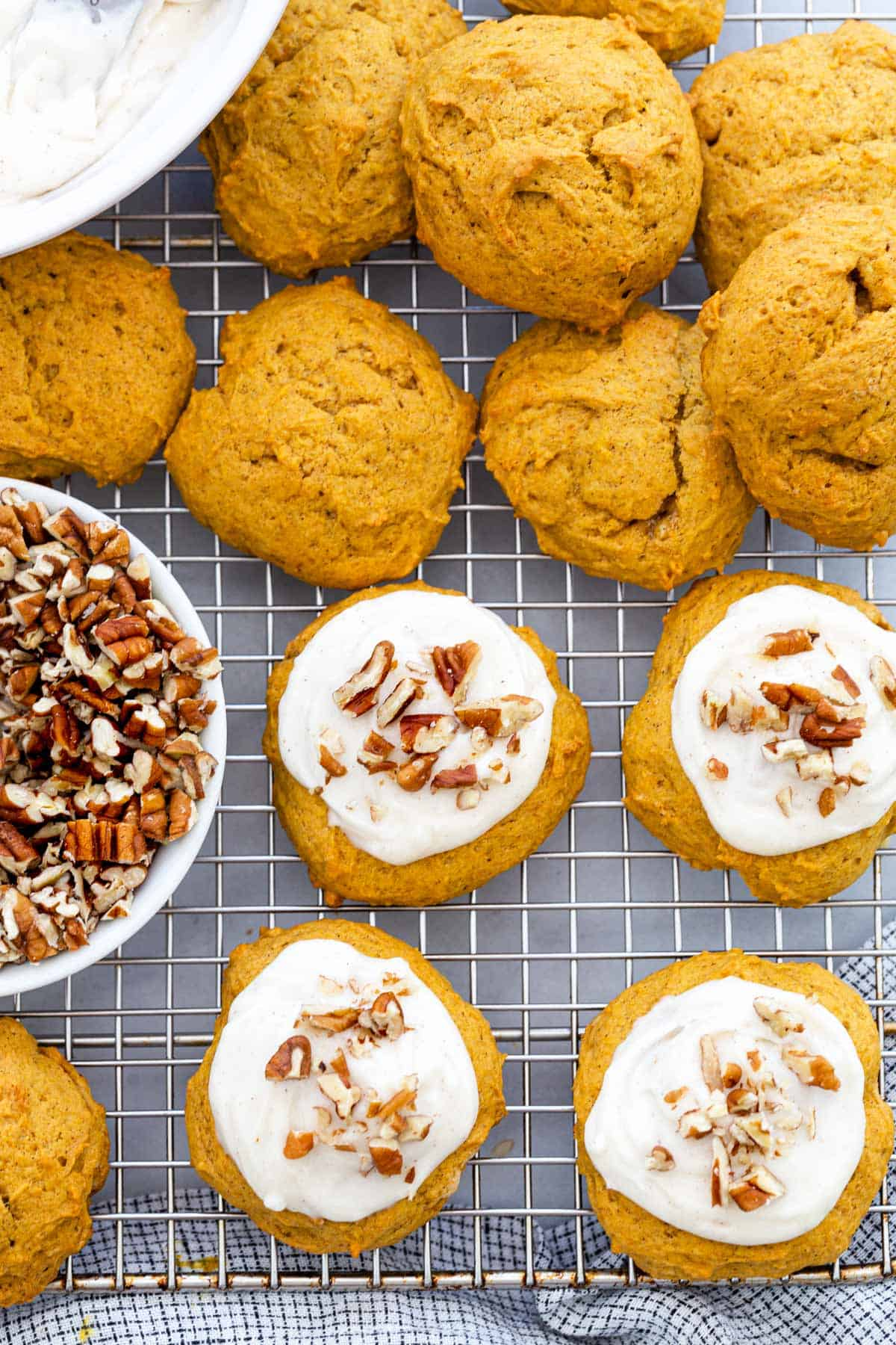 Pumpkin cookies topped with a smooth cream cheese frosting and chopped pecans. Pumpkin puree gives these treats their characteristic orange color. #pumpkin #pumpkincookies #fallrecipes
