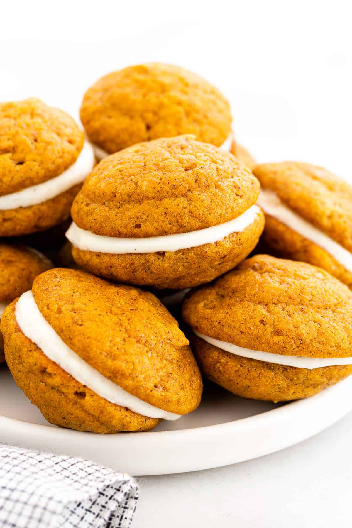 Pumpkin whoopie pies stuffed with a frosted cream cheese filling. Pumpkin puree adds a mildly sweet flavor and creates a bright orange color. #whoopiepies #pumpkin #pumpkincookies