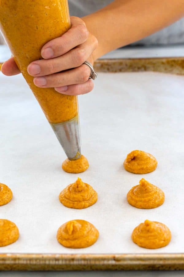 Piping cookie dough batter onto parchment paper