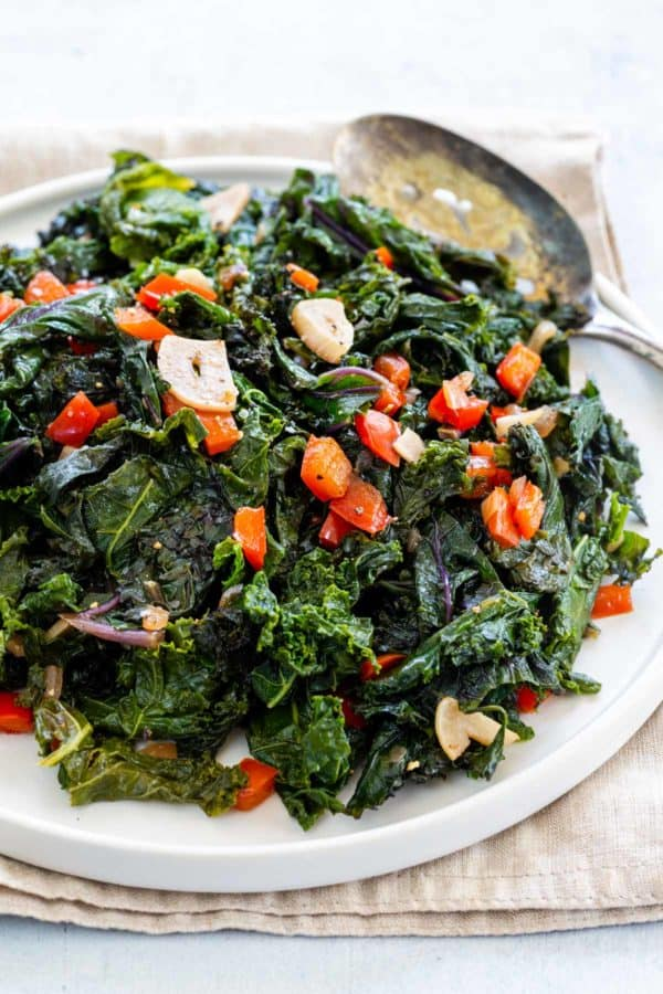 sauteed kale served with diced tomatoes and crushed garlic on a plate