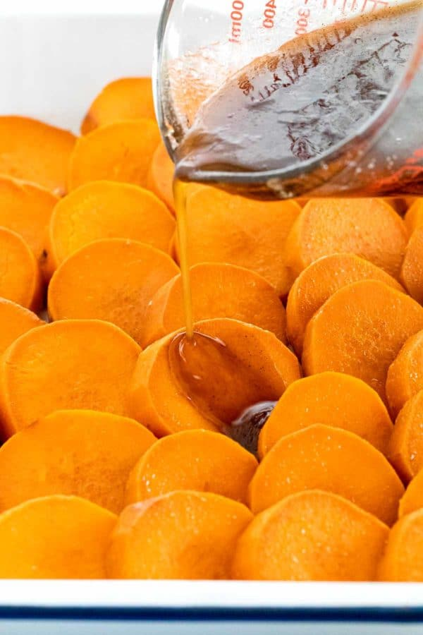 pouring glaze over slices of sweet potatoes in a baking dish