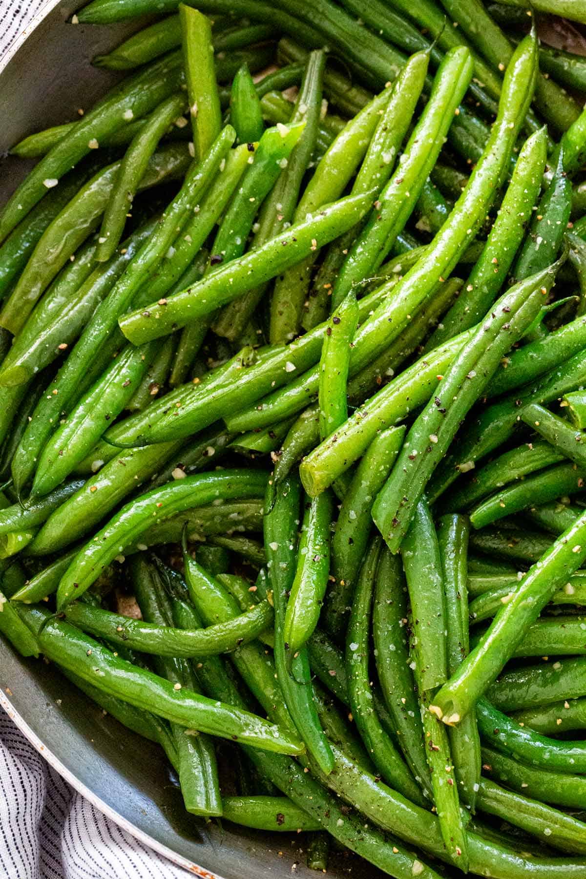 Sautéed greens beans are a healthy side dish. To make this an easy one-pan recipe, saute garlic and beans first and then steam until crisp-tender. #greenbeans #sidedish #healthyrecipe
