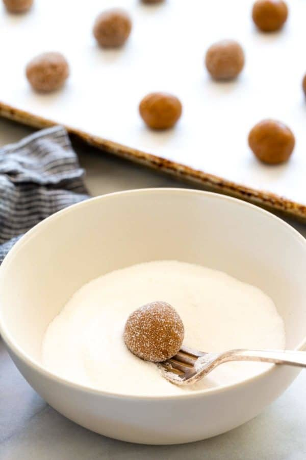 Coating cookie dough balls in a bowl of granulated sugar
