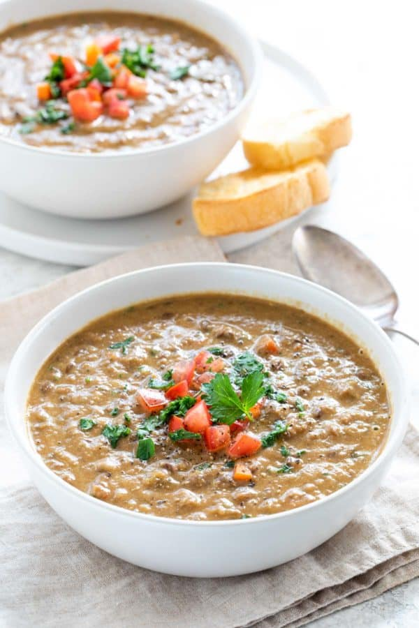 two bowls of lentil soup served with crunchy slices of bread