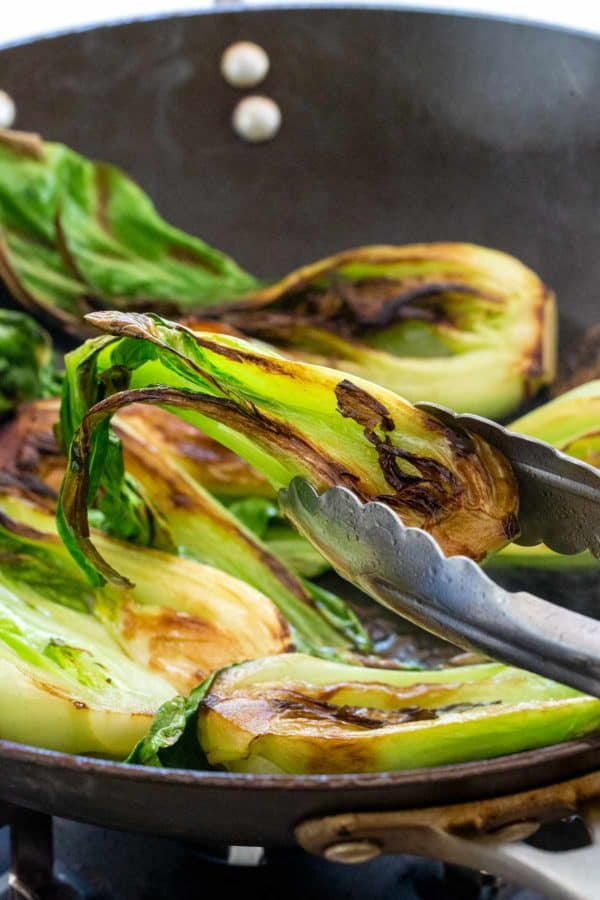sauteed bok choy pieces cooking in a wok