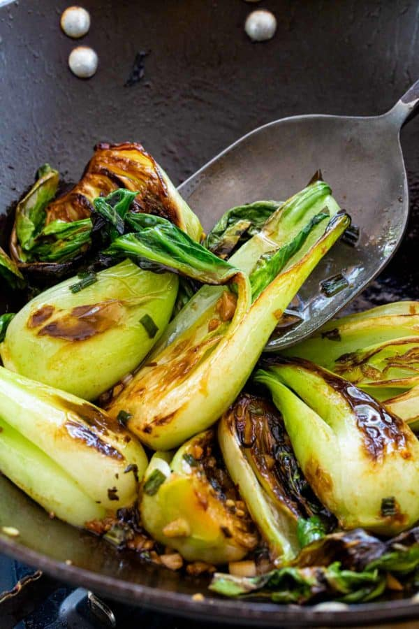 wok spatula stirring together sauce and bok choy