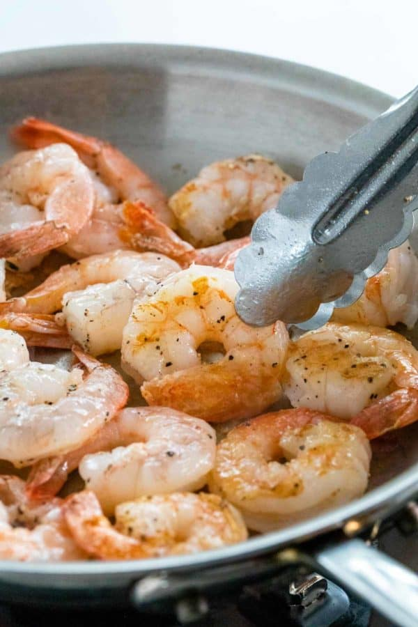 metal tongs flipping over partially cooked shrimp in a pan