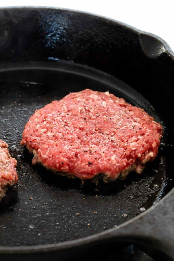 seasoned burger patty cooking in a cast iron skillet