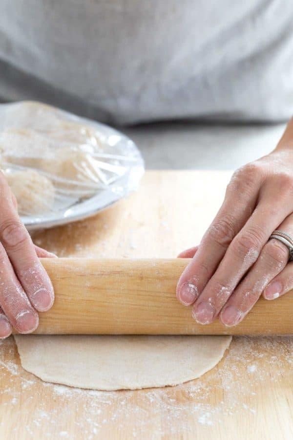 Using a rolling pin to flatten dough into a round tortilla