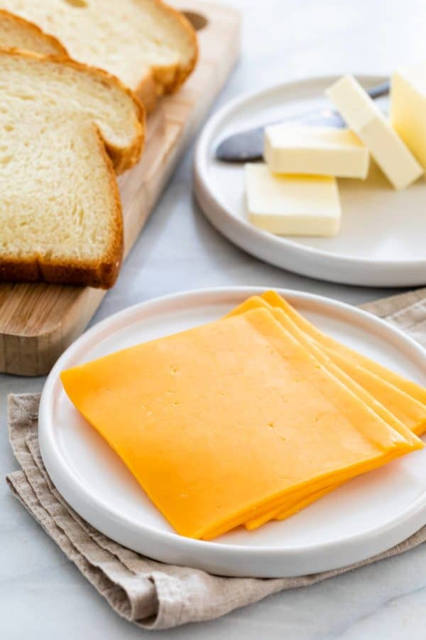 slices of cheese, bread, and butter on a table