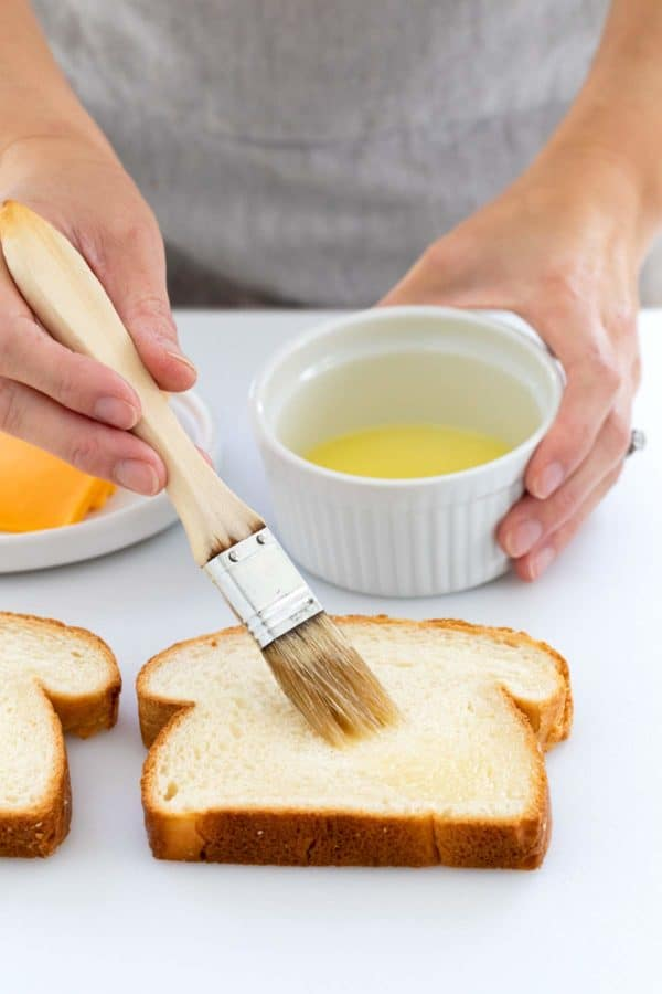 person brushing melted butter on a slice of white bread