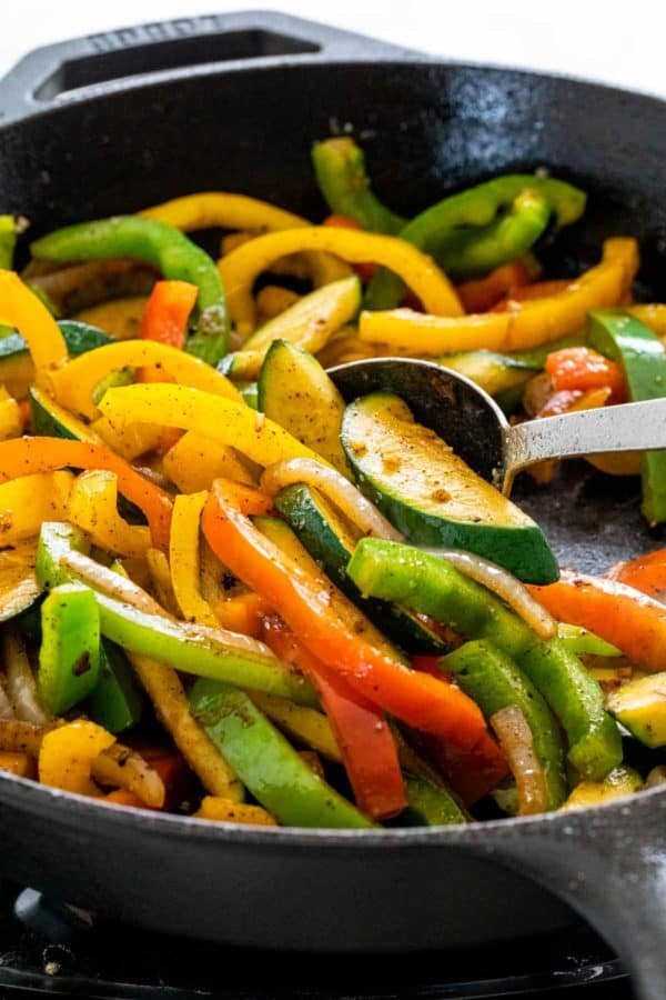 slices of bell peppers and zucchini cooking in a large skillet