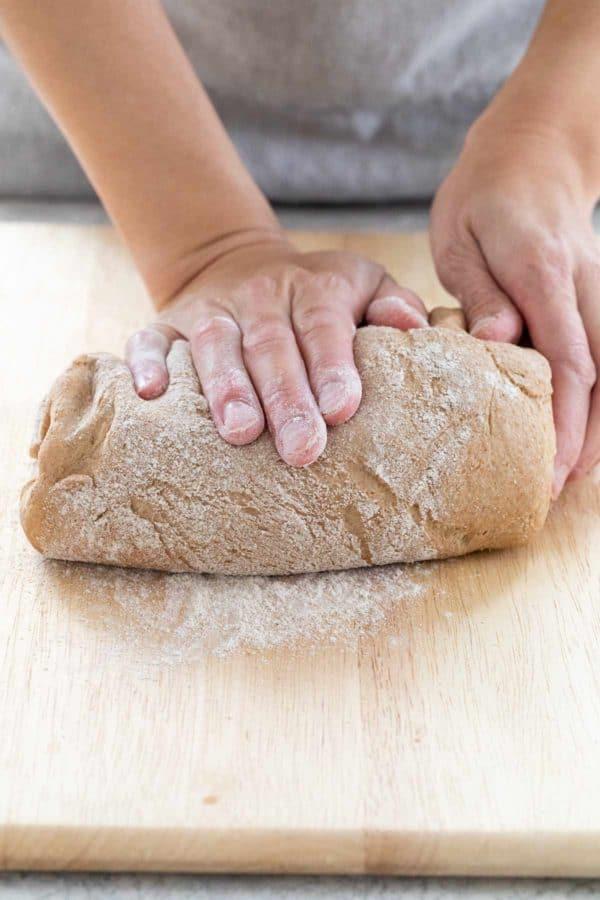 kneading dough on a floured surface