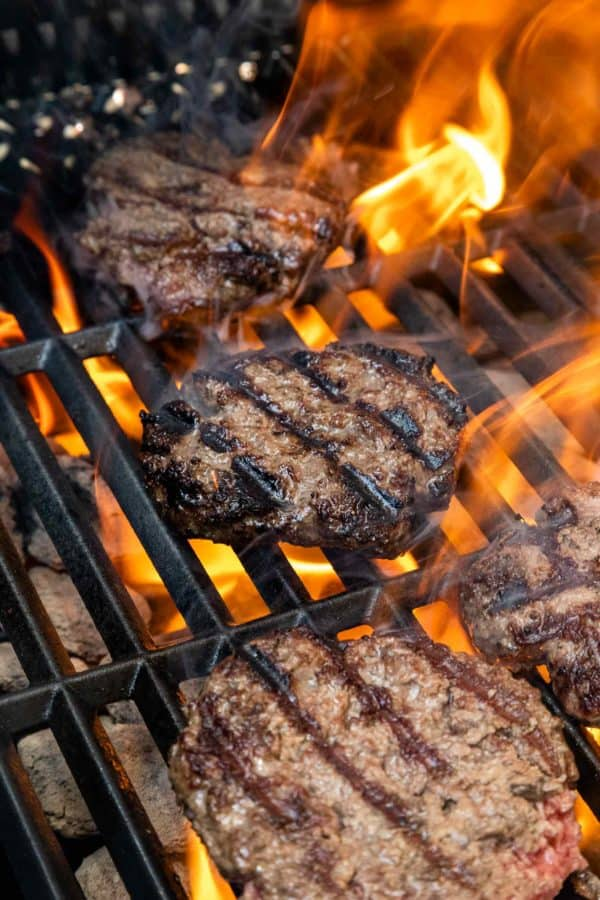 burgers grilling with flames