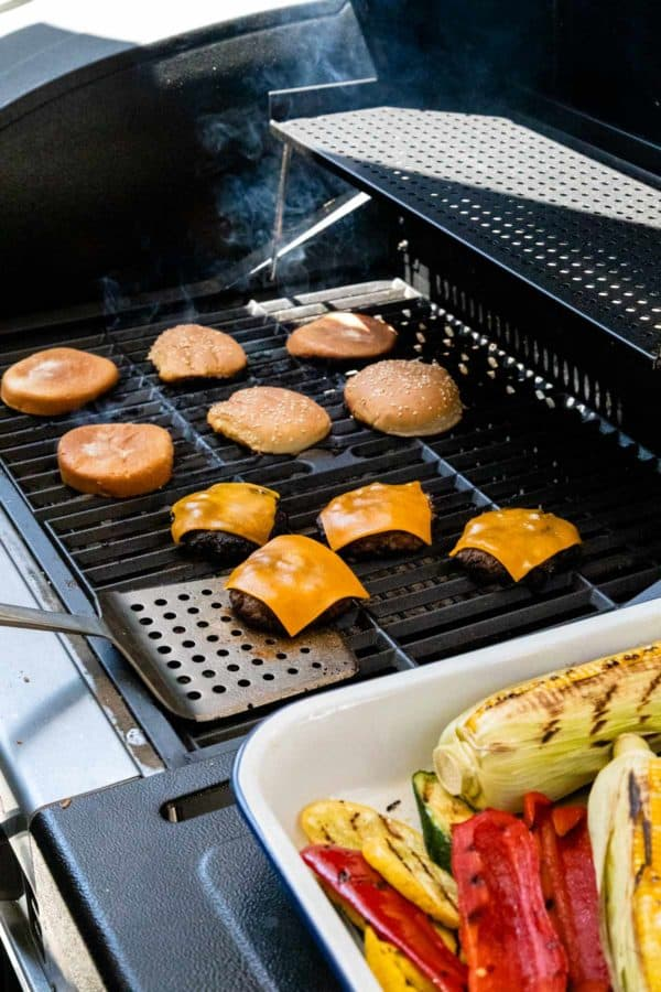 melting slices of cheese on burger patties on the grill