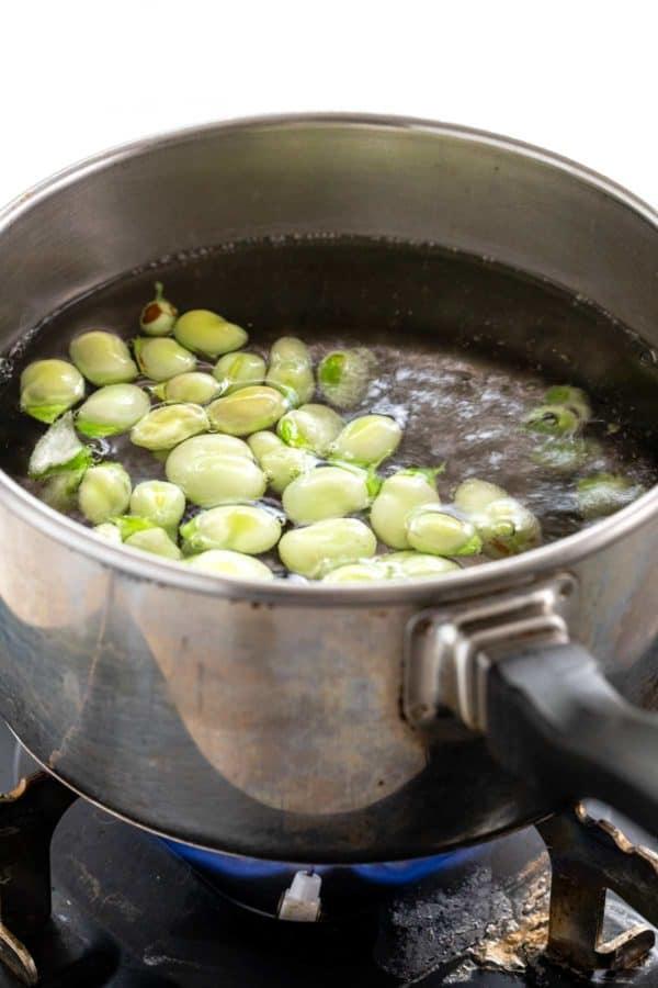 Fava beans boiling in a saucepan
