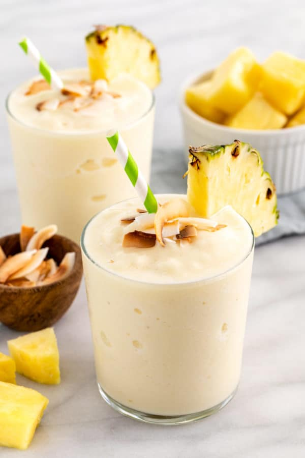 Two glasses of smoothies with slices of pineapple on the cup