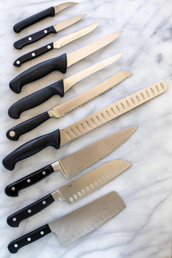 Different types of kitchen knives spread out on a table