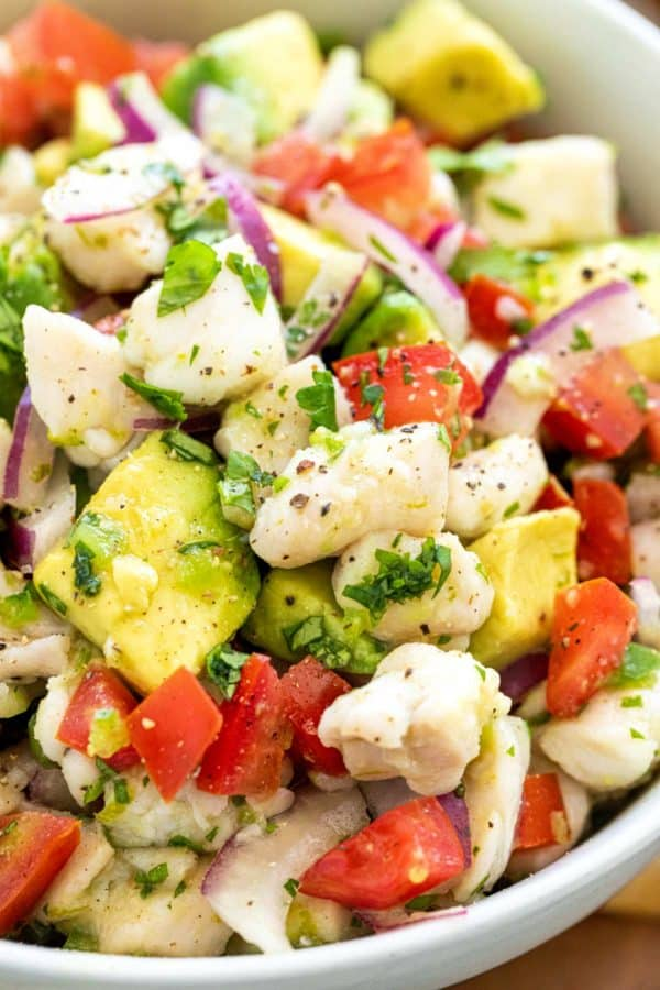 Close up of fish ceviche with cubed tomatoes and diced pieces of avocado