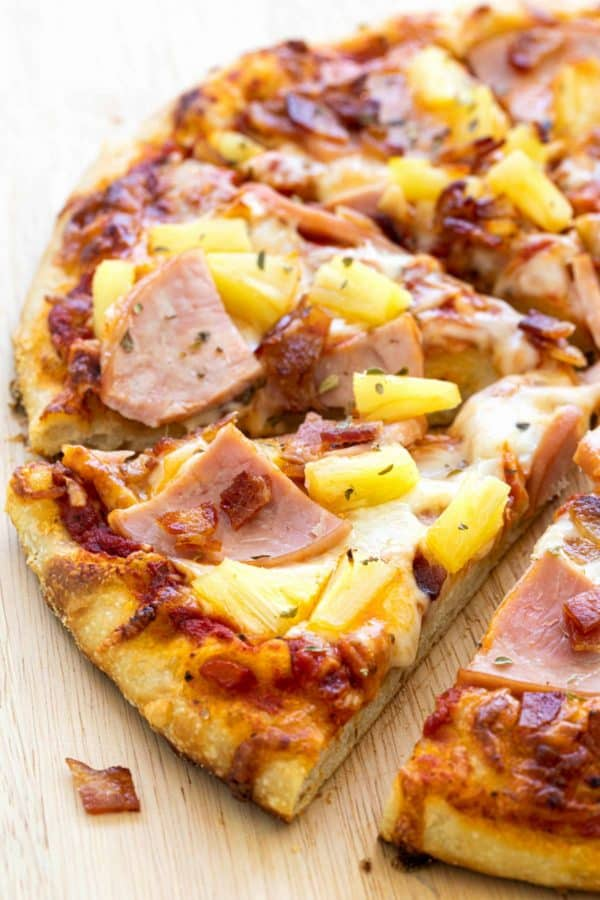 Close up of a slice of Hawaiian pizza on a cutting board