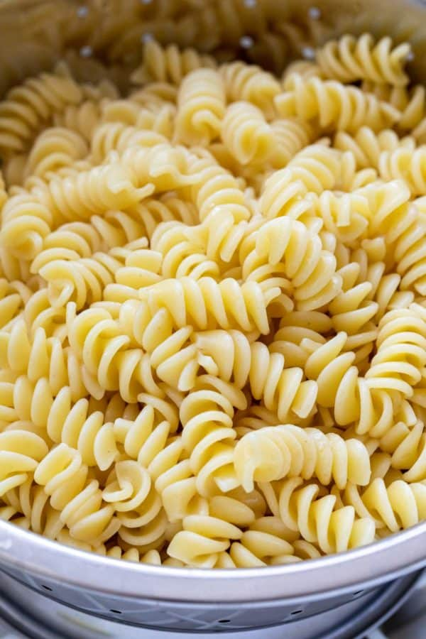 Pasta noodles being drained in a colander