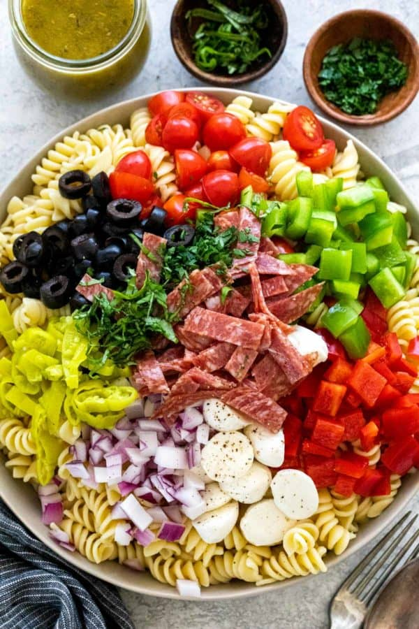 Unmixed pasta salad in a bowl with vegetables, cheese, and salami
