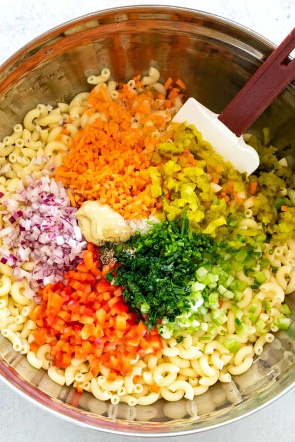 mixing bowl filled with diced vegetables and pasta noodles