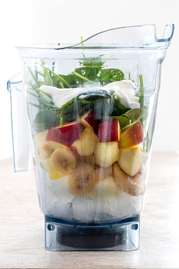 Side view of a blender cup filled with spinach, apples, and bananas