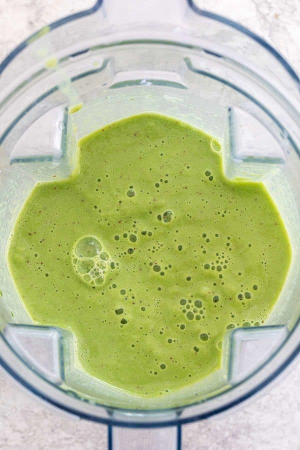 Top down view of a blender cap with pureed spinach smoothie inside