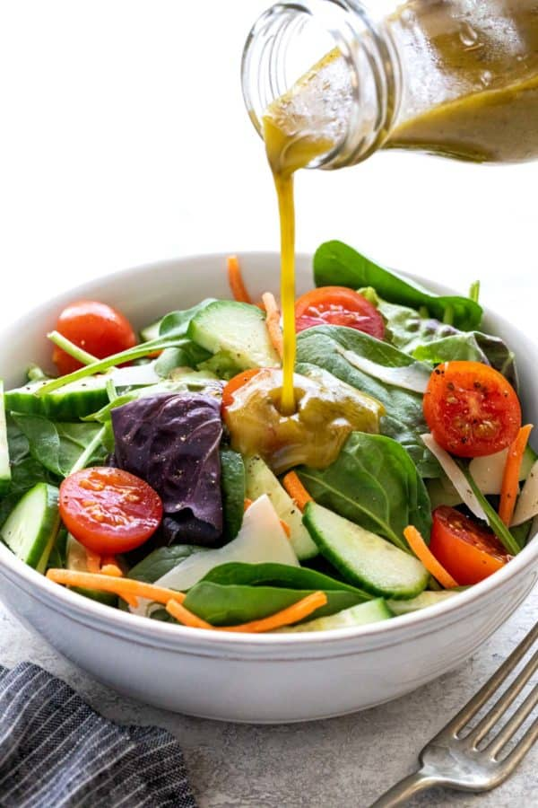 Pouring italian dressing over a bowl of salad