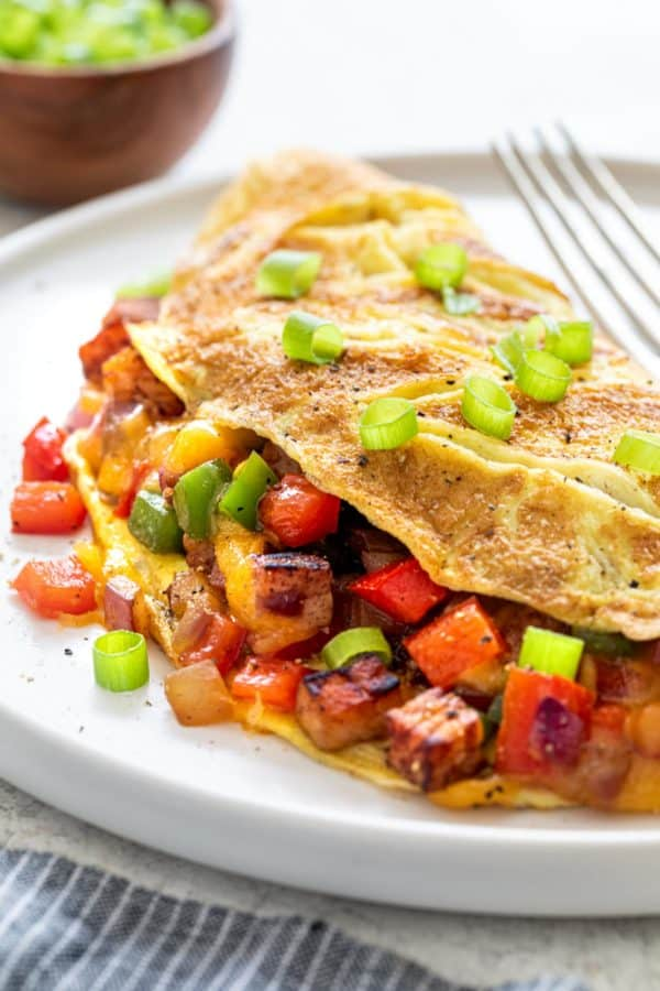 Denver omelet on a plate with green onions on top
