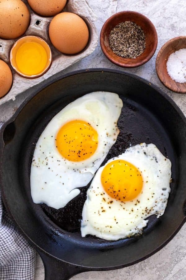 two fried eggs in a cast iron skillet