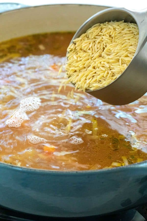 Adding orzo pasta into a pot of soup