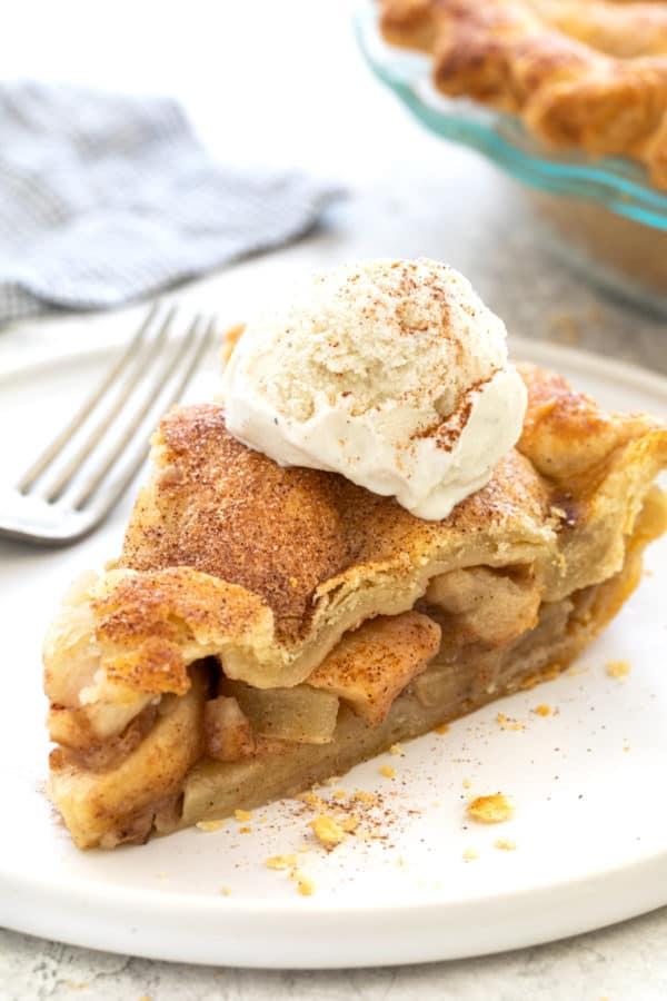Slice of apple pie with a scoop of vanilla ice cream on top