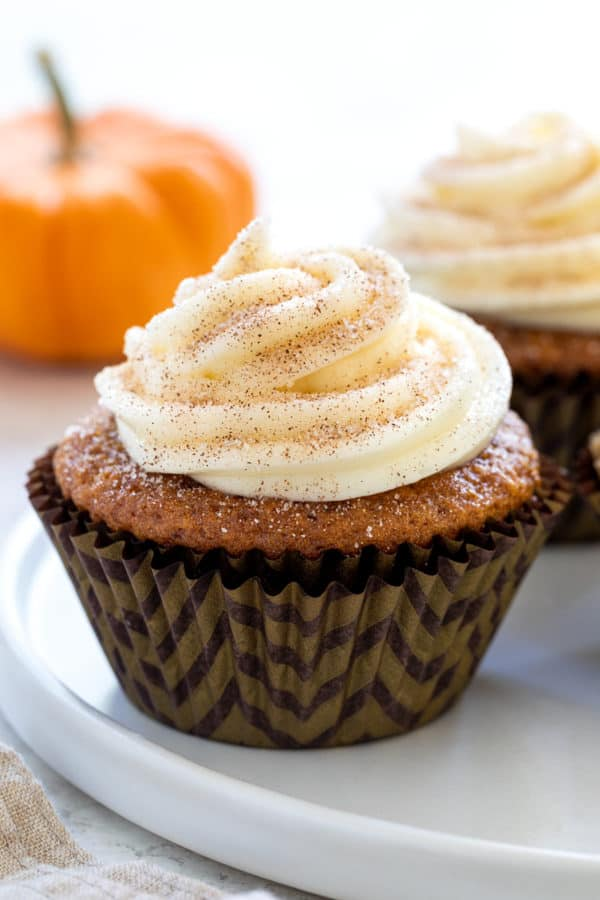 Pumpkin cupcake with a swirl of cream cheese frosting on top