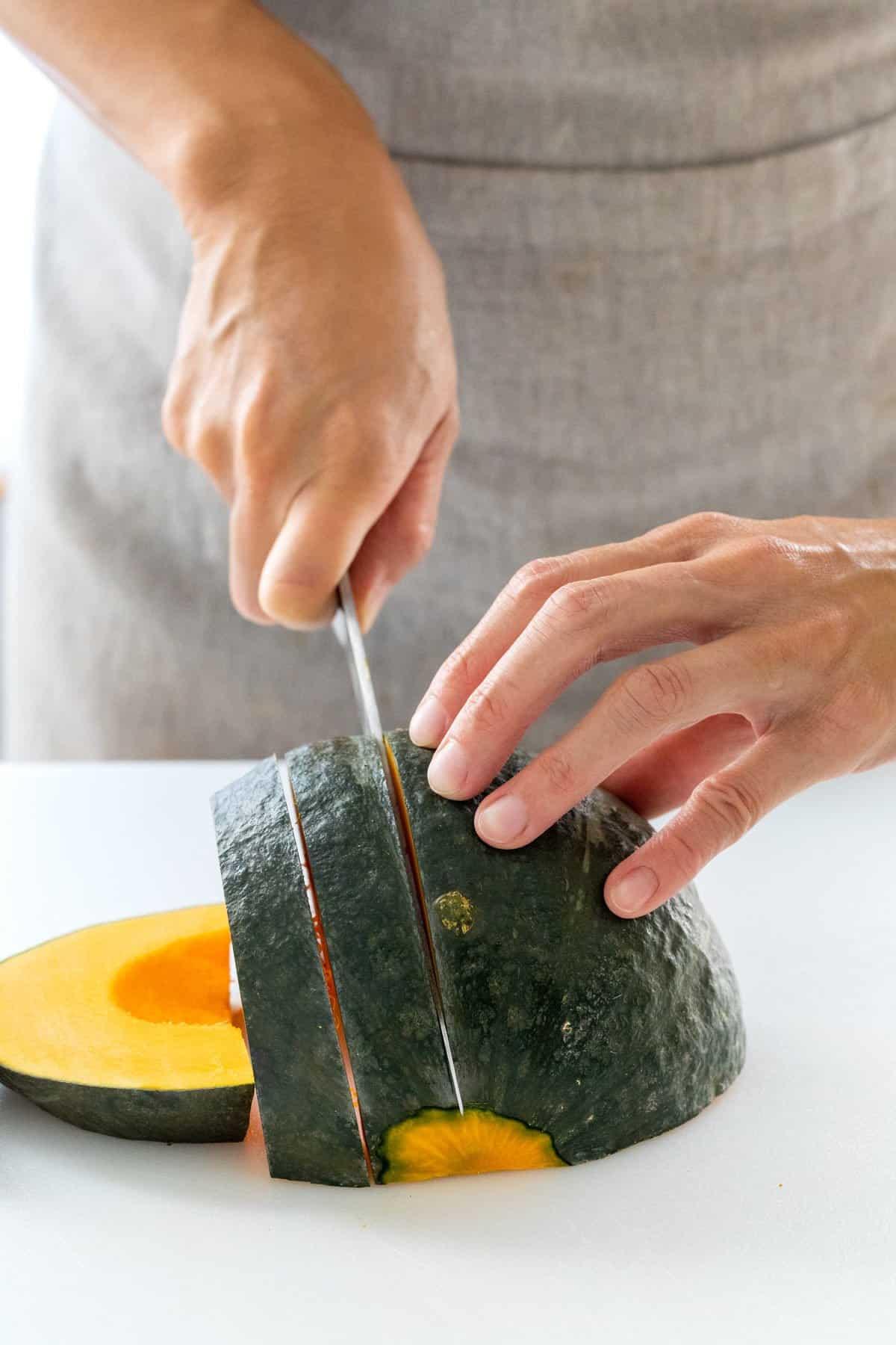 Slicing kabocha squash into smaller pieces