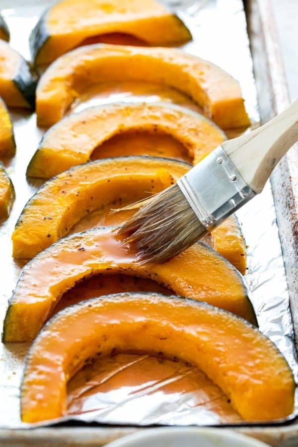 Brushing glaze on slices of squash on a sheet pan