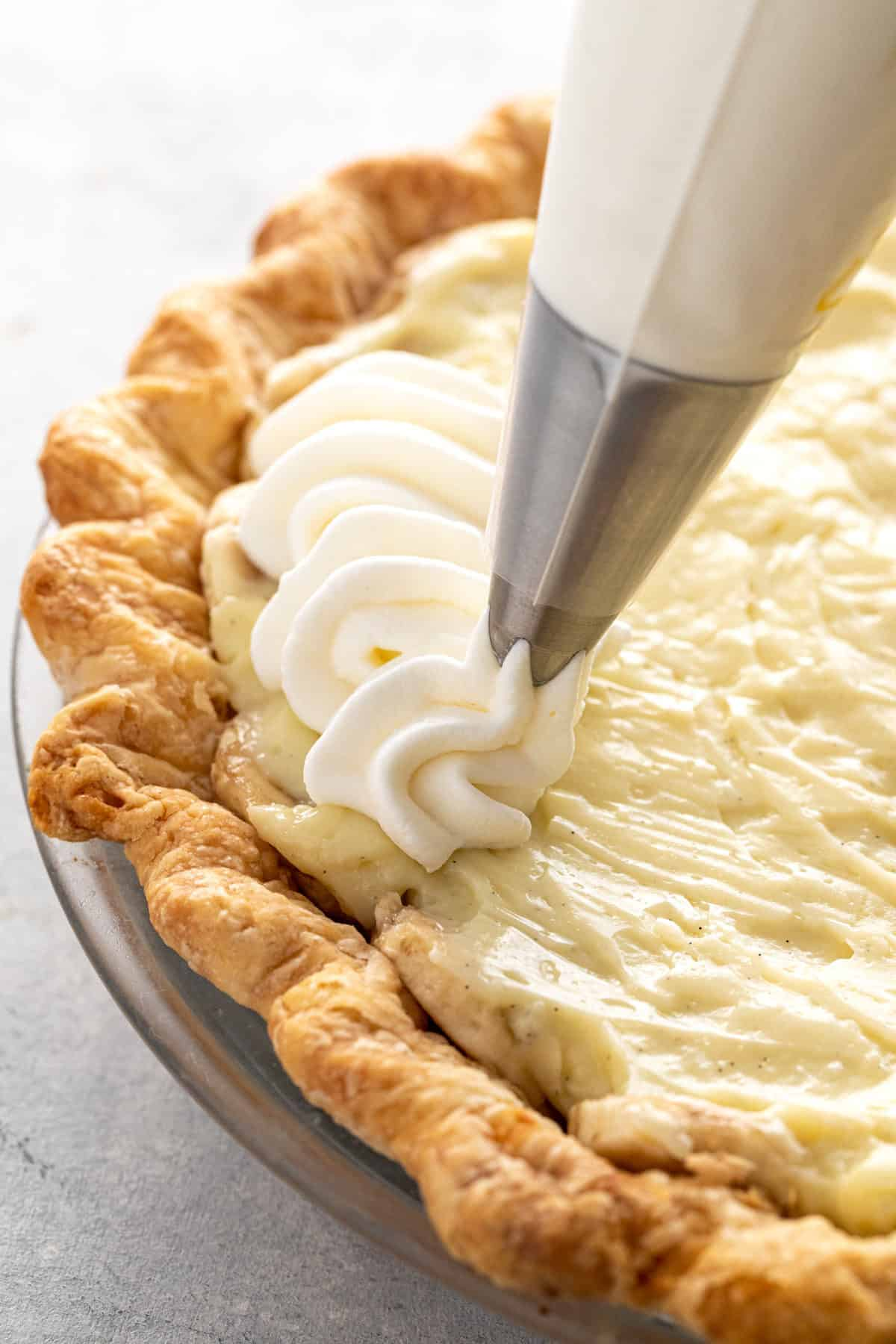 Piping whipped cream on top of a pie