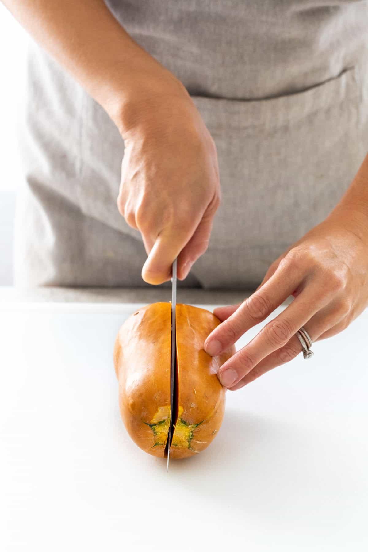 Slicing a honeynut squash length-wise