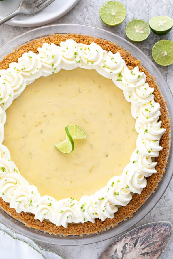 Top down photo of a key lime pie with whipped cream pipped around the edge