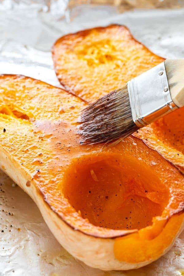 Brushing a maple glaze over roasted butternut squash
