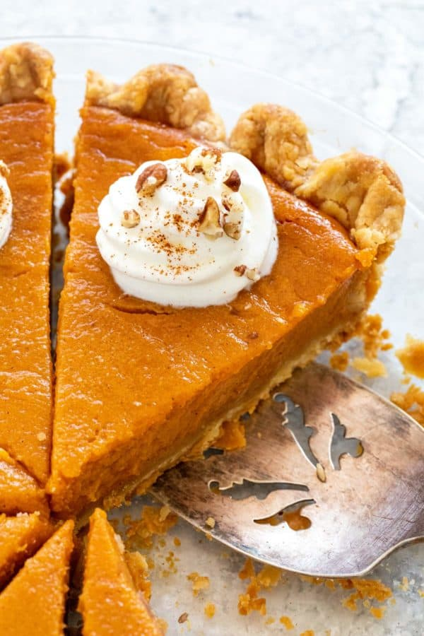 Sweet potato pie with whipped cream and nuts on top