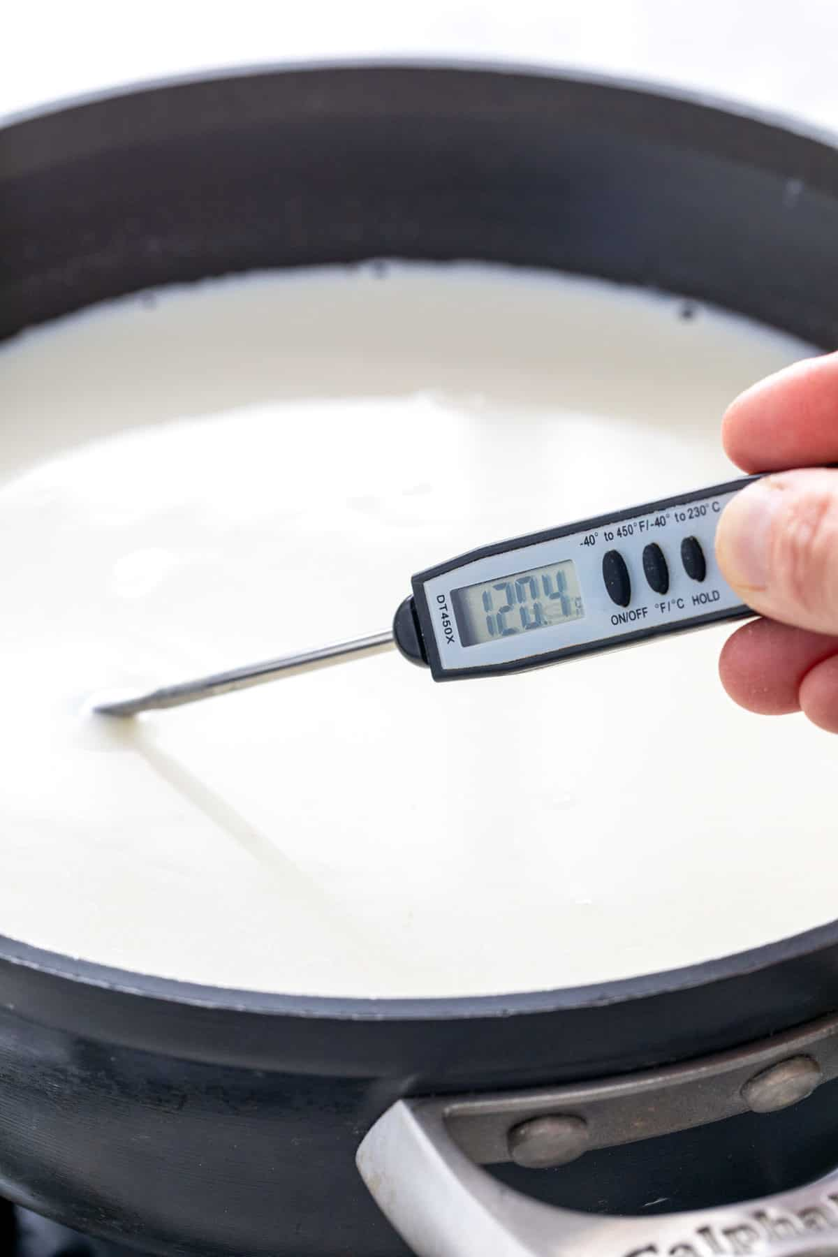 checking the temperature of milk in a saucepan